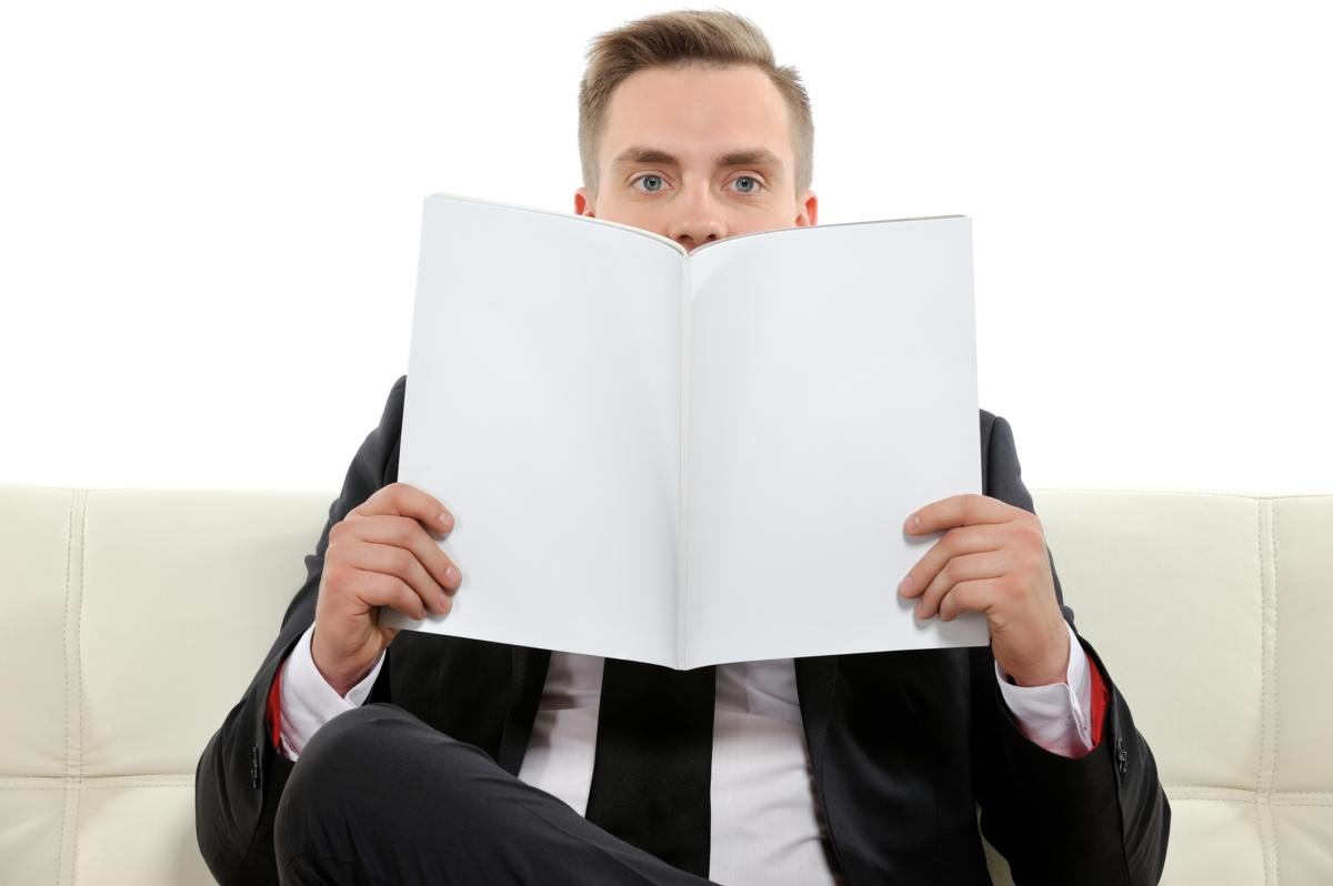 Man sitting on white sofa holding reading paper in front of face