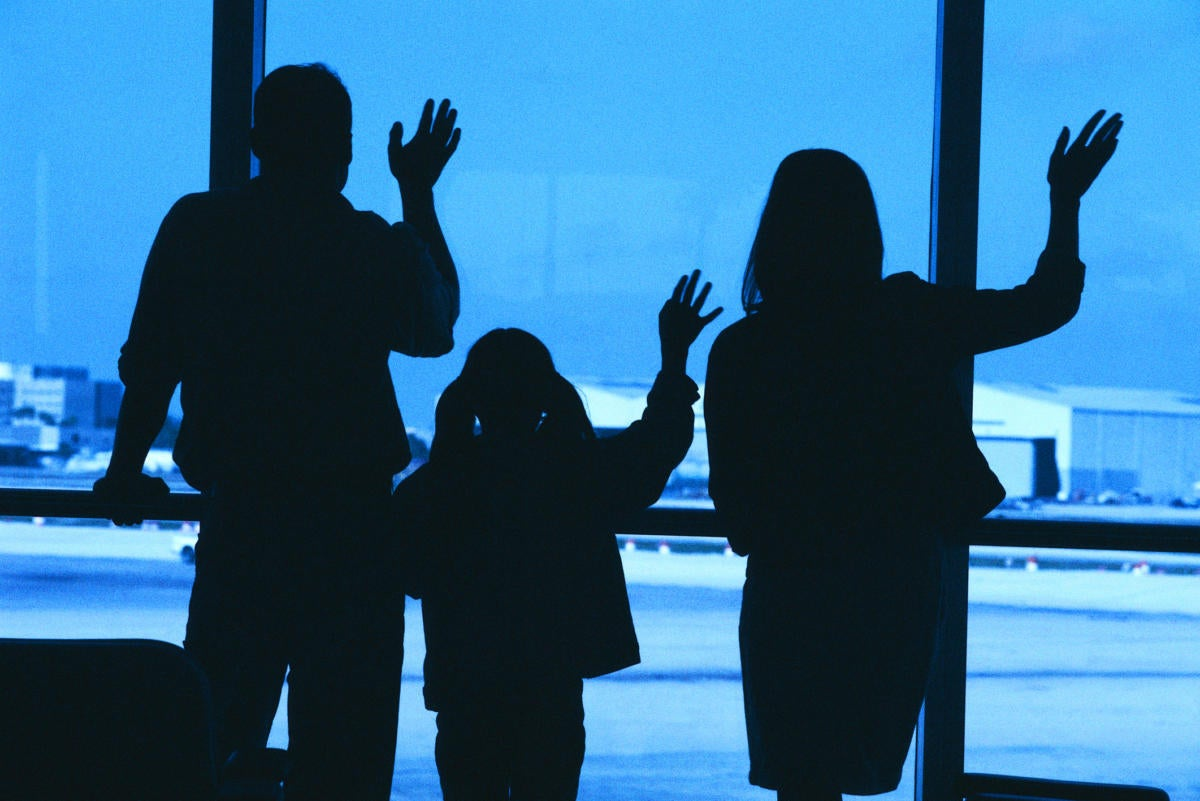 Family in silhouette waving goodbye at airport
