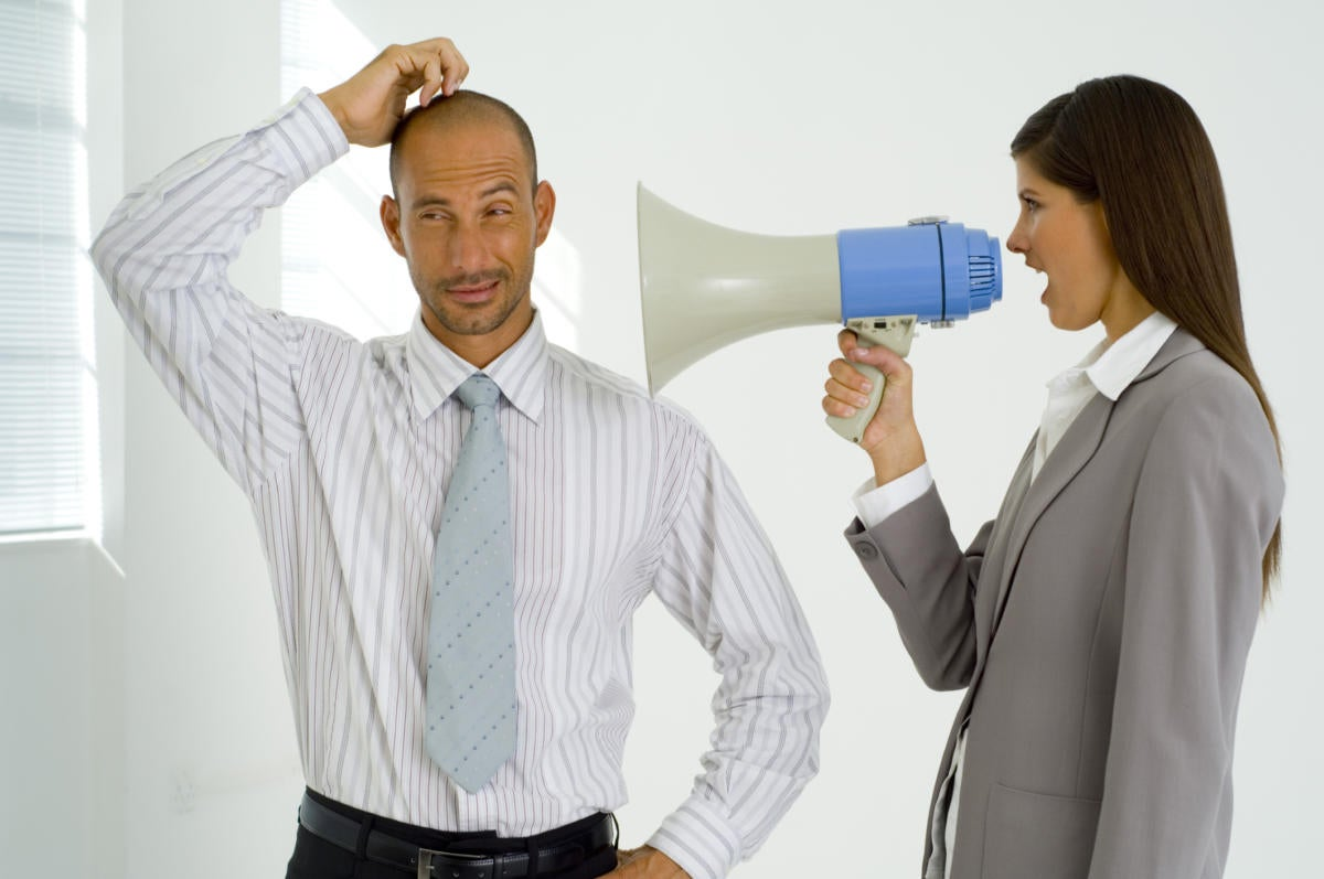 Woman executive yelling into megaphone at man.