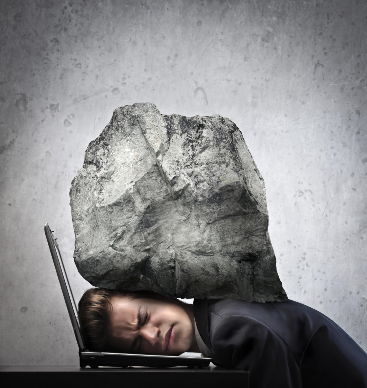 Man being crushed by large rock on top of laptop feeling stressed overworked