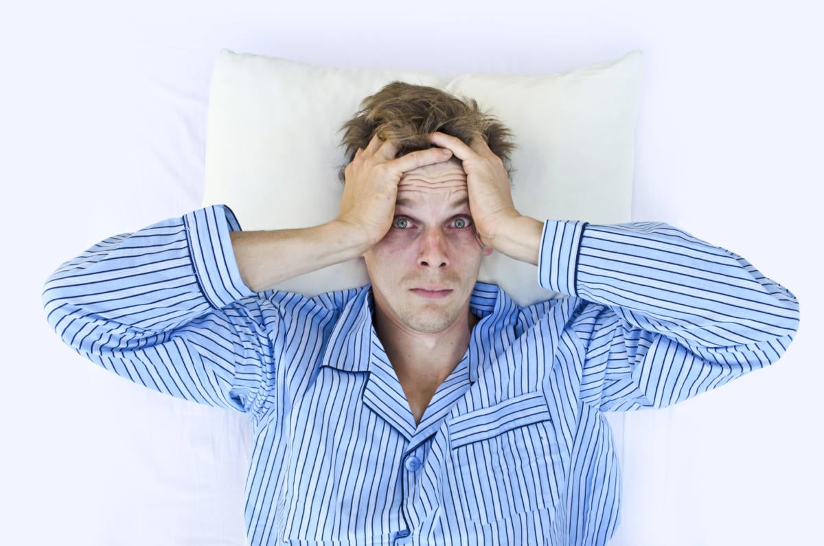 Man in pajamas in bed unable to sleep insomniac