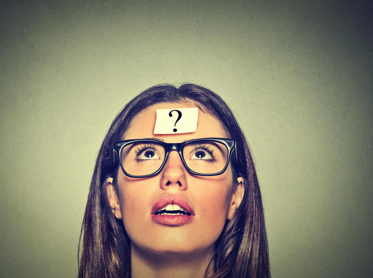 Women with glasses looking up with question mark on a post-it on forehead