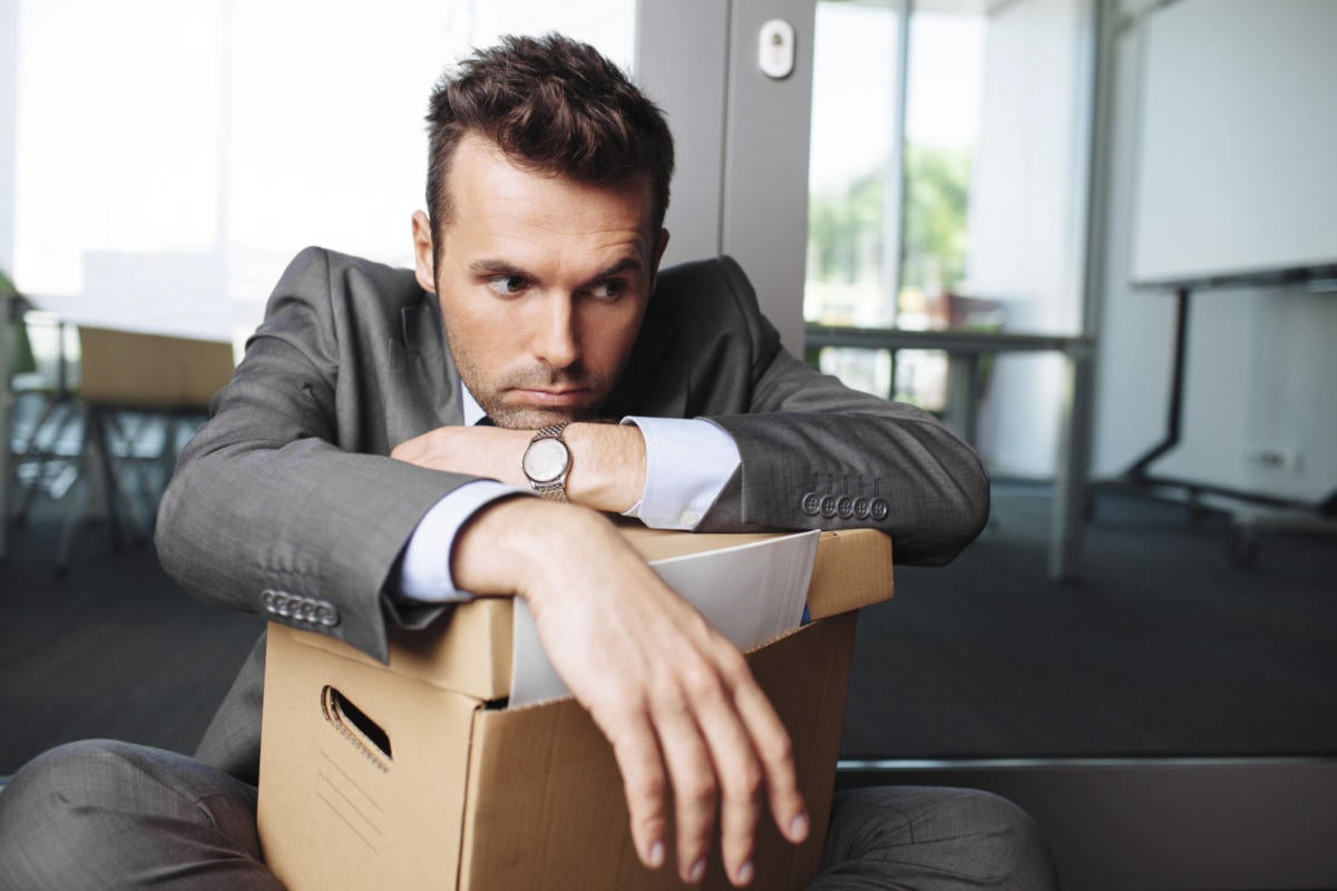man leaning on box of office belongings after being fired or laid off