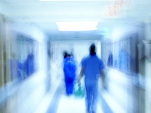 Hospital scene with medical staff in blue scrubs blurred