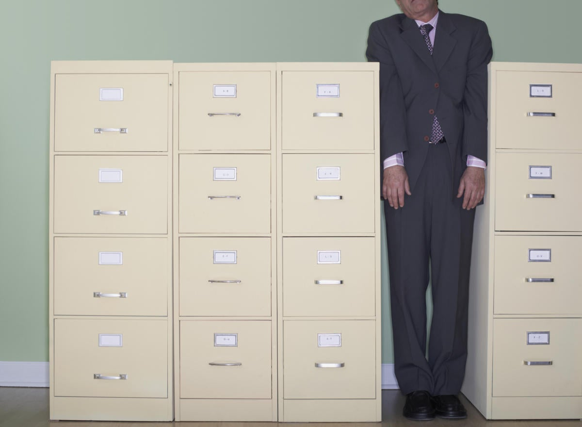 Man squeezed between file cabinets