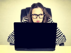 A paranoid user with a laptop computer looks around suspiciously. [credit: Thinkstock]