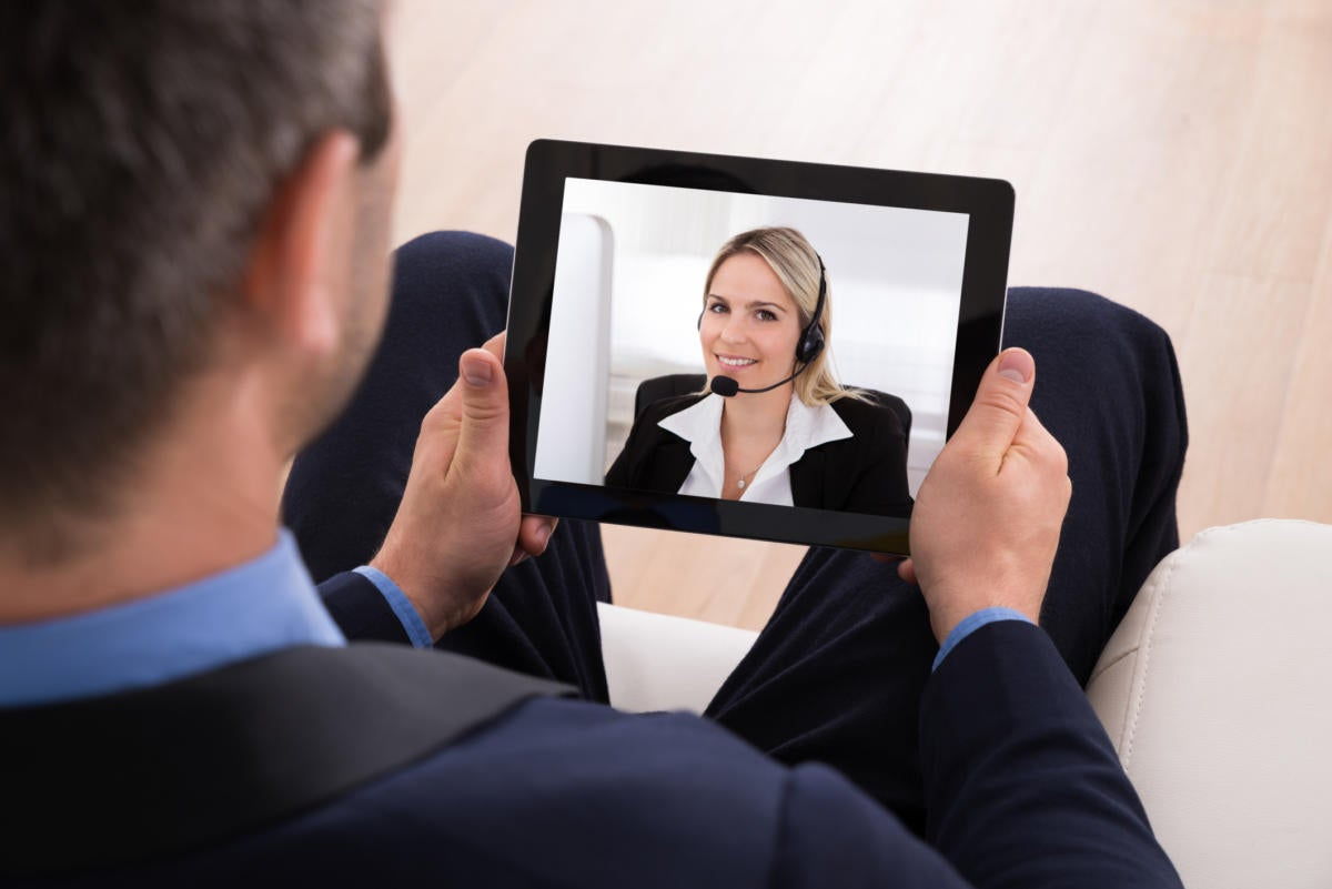 Man in suit videoconferencing on tablet