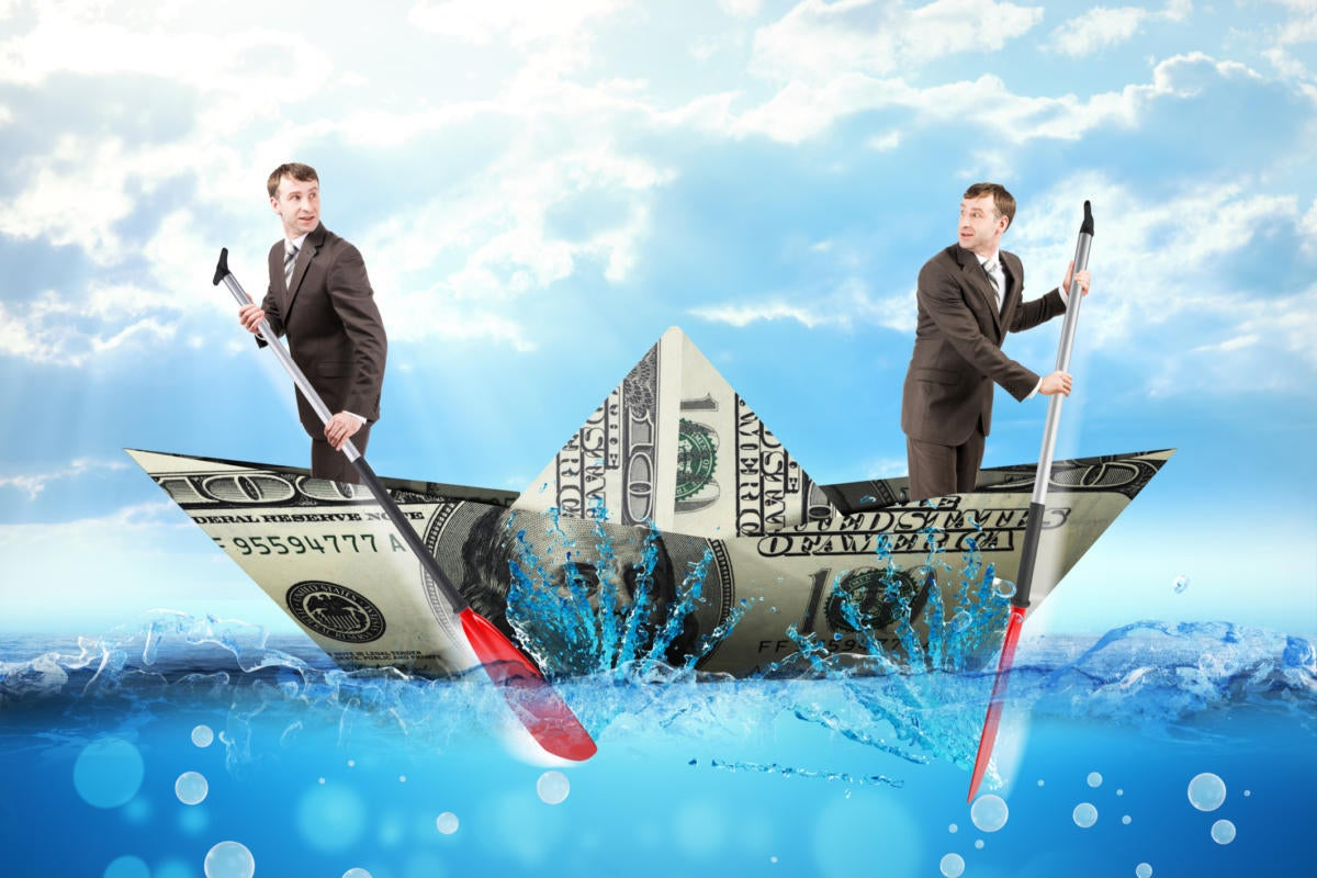Two men paddling boat made of money against blue sky