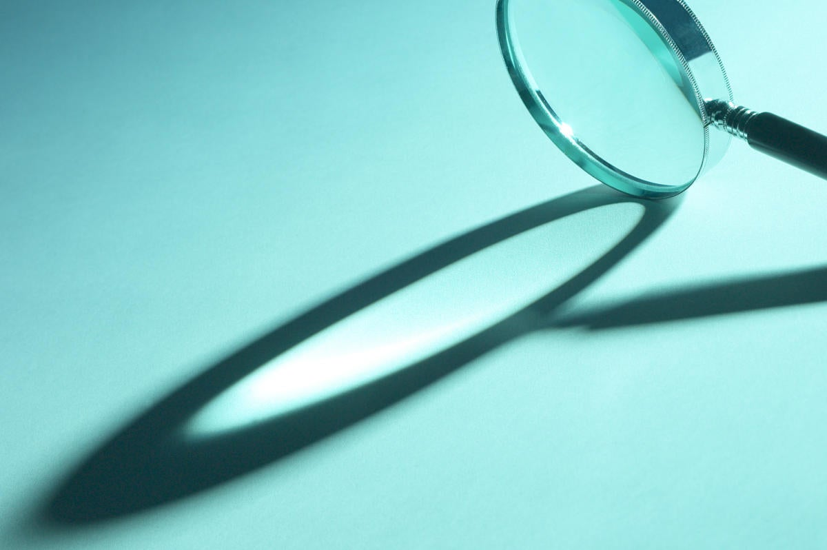 magnifying glass on teal background with shadow