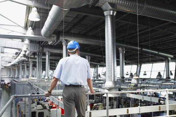 businessman in hardhat looking at factory floor 000024361936 medium