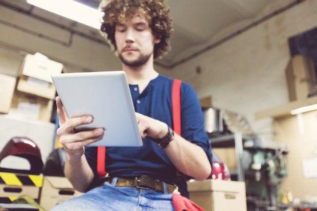 man in a workshop using a digital tablet 000091629367 medium