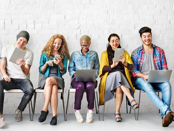group of millennials using mobile devices