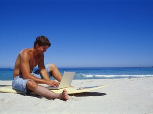 Man sitting on surfboard on beach with laptop