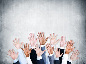 Group of hands raised to volunteer