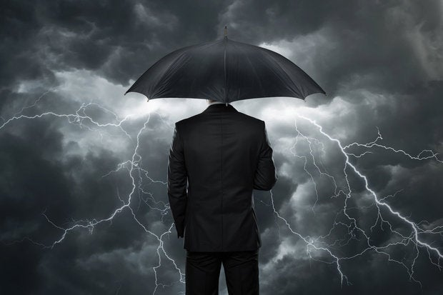 Man in black suit from behind holding umbrella with stormy skies