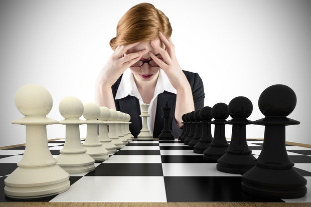 Woman looking down with chess pieces in front of her