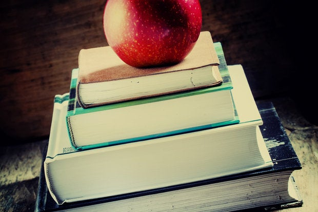 Stack of school books on desk with an apple on top