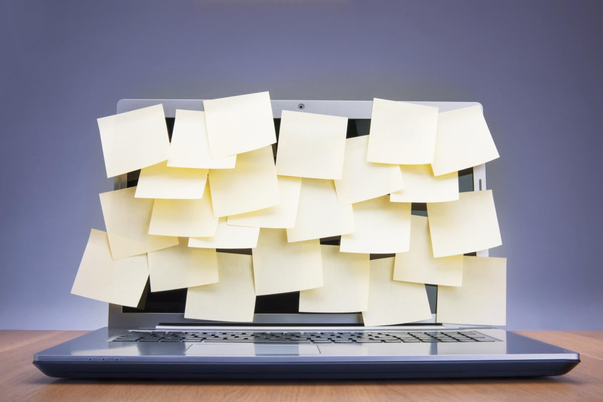 laptop covered with sticky notes