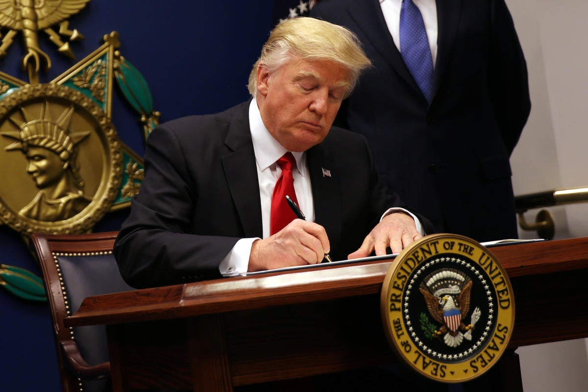 President Donald Trump signs an executive order to impose tighter vetting