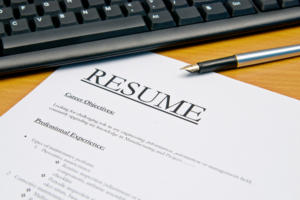 Resume with pen and laptop on desk