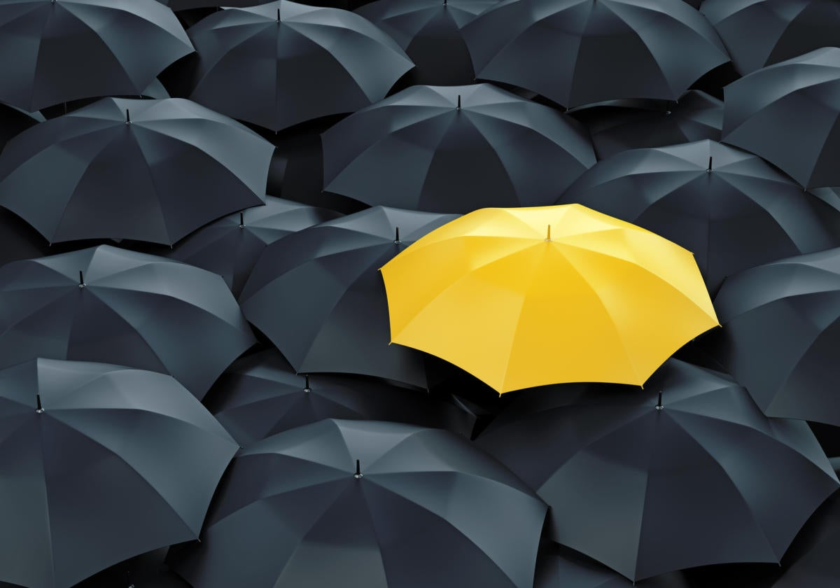 Yellow umbrella among many black umbrellas