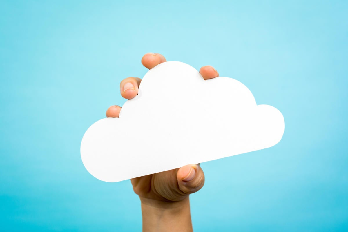 Hand holding paper cloud with blue background