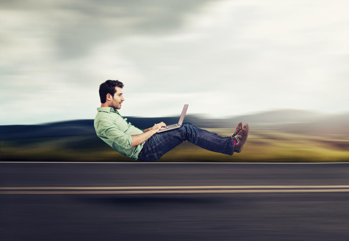 hipster with laptop speeding along road