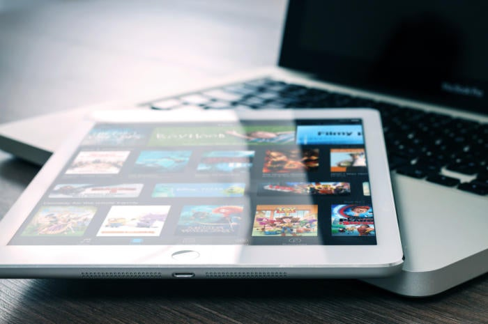 iPad displays iTunes store while resting on MacBook, by William Iven [CC0 via Unsplash]