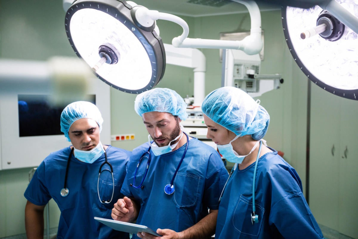 3 doctor surgeons in operating room on tablet