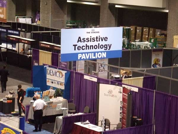 Picture of a convention floor, with a sign reading Assistive Technology Pavilion