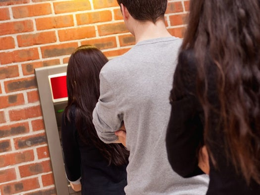 Man watching person at ATM