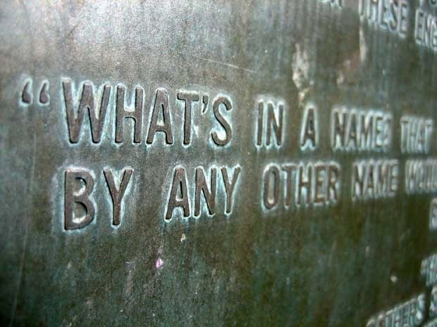 A close up words engraved in a wall. We only see parts of sentences. The first line says What\'s in a name that... Second line says By any other name would...