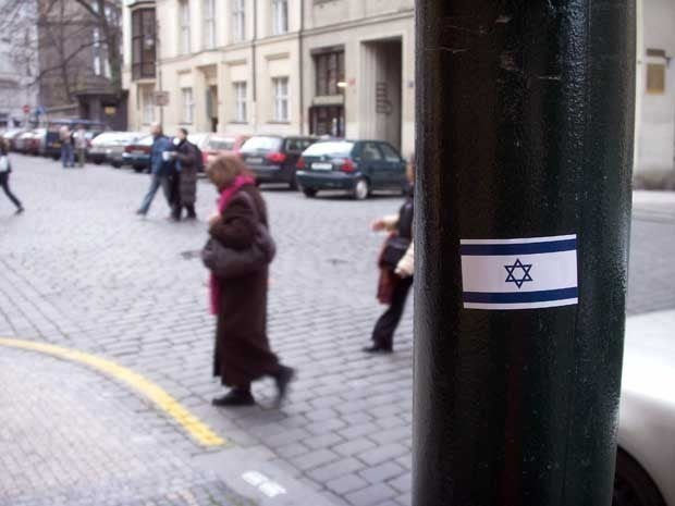 PIcture of a street corner with an Israeli flag sticker on a utility pole.