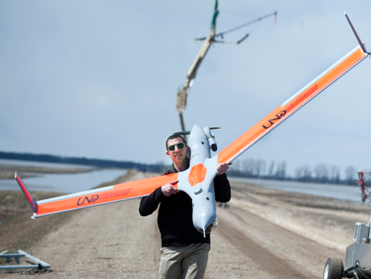 student holding a Boeing Scan Eagle unmanned aircraft