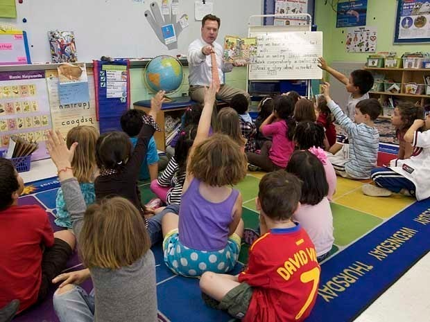 Picture of a man teaching a classroom of little kids