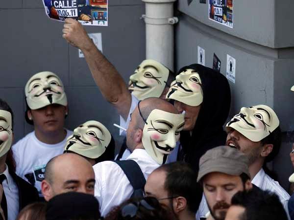 Demonstrators wearing anonymous masks crowd Neptuno plaza near Spanish parliament in Madrid June 19,