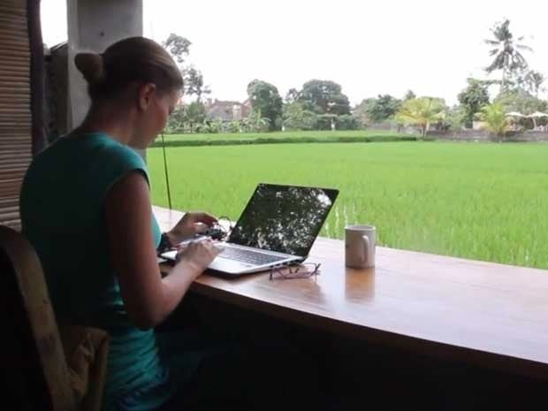 Picture of a working at a laptop at Hubud offices, overlooking a rice paddy