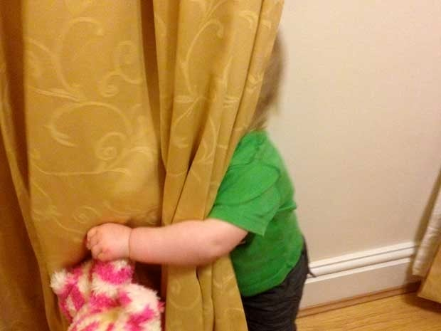 Small child hiding behind a curtain